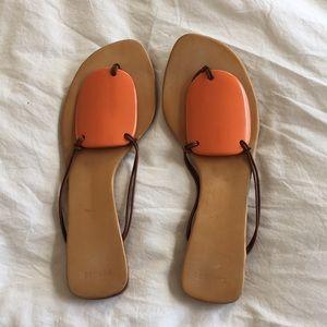 Hermes sandals with iconic orange ceramic center.